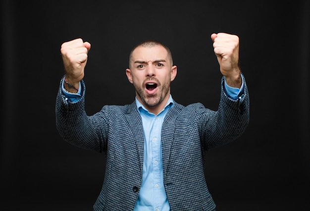 Célébrant un succès incroyable comme un gagnant, l'air excité et heureux en disant: prenez ça!