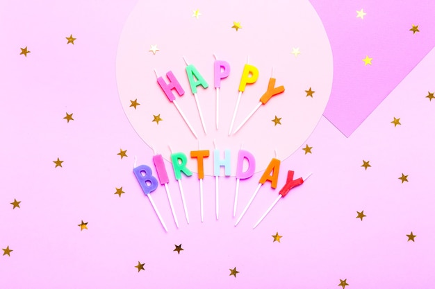 Célébration colorée avec divers confettis de fête, ballons, banderoles, feux d'artifice et décoration sur rose.