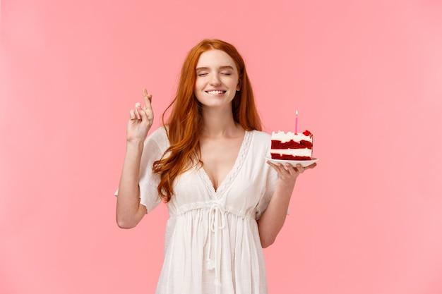 Célébration, concept de bonheur. jolie rousse rêveuse dans une jolie robe blanche, tenant un gâteau du jour b, croise le doigt bonne chance, mord la lèvre en tentant de fermer les yeux et en souhaitant souffler la bougie