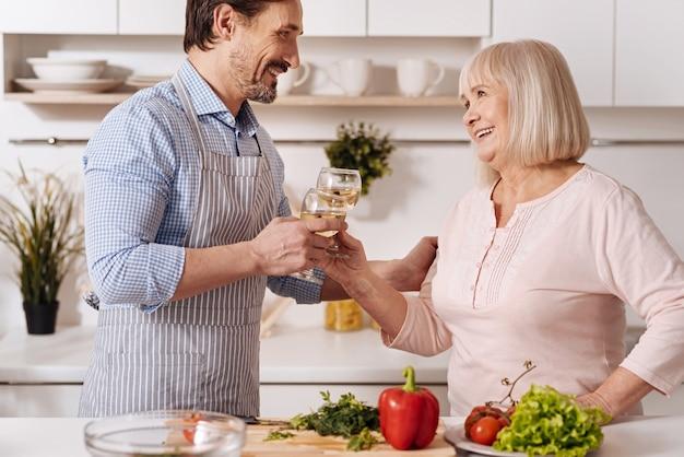 Célébration de la diversité des générations. homme barbu charmant positif debout dans la cuisine et profiter du week-end tout en buvant une boisson avec sa mère aînée