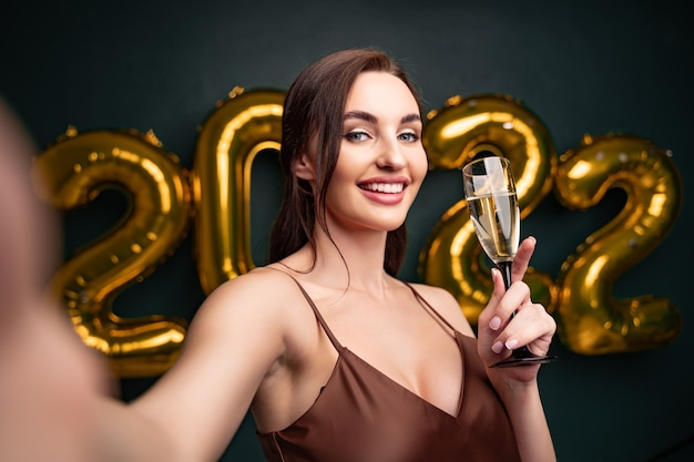 Célébration du nouvel an belle femme brune faisant selfie devant des ballons dorés backg noir...