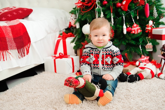 Célébration du nouvel an en famille. le petit boyl à l'arbre de noël.