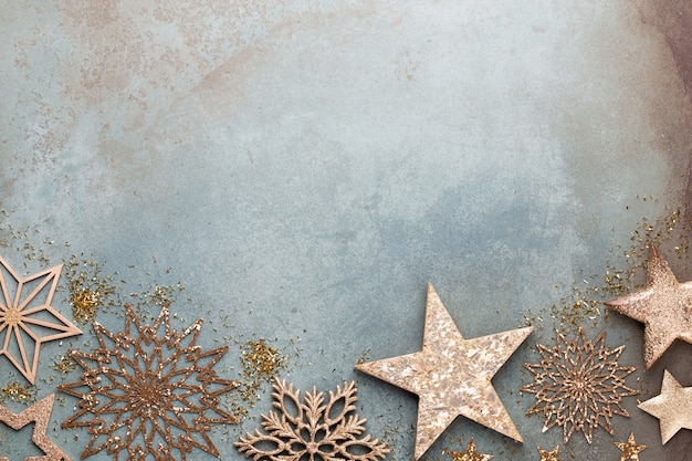 Célébration du nouvel an et fond de noël avec des fleurs dorées, de la neige, des étoiles et des décorations de noël vue de dessus.