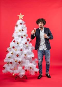 Célébration du nouvel an avec jeune homme barbu avec du vin debout près de l'arbre de noël blanc décoré sur le rouge
