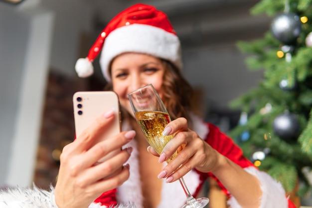 Célébration du nouvel an et de noël sur la distance du concept. une jeune femme en costume et chapeau de père noël tient un smartphone sur fond de sapin décoré.
