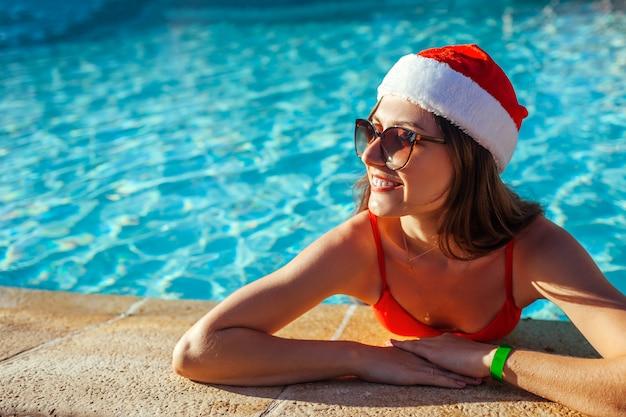 Célébration du nouvel an et de noël. femme au chapeau du père noël et bikini se détendre dans la piscine. vacances tropicales