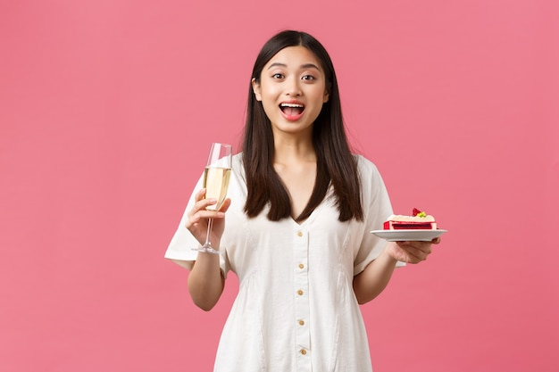 Célébration, fêtes et concept amusant. belle femme rêveuse célébrant son anniversaire avec du champagne en verre et un gâteau d'anniversaire, l'air surprise et excitée, debout sur fond rose.