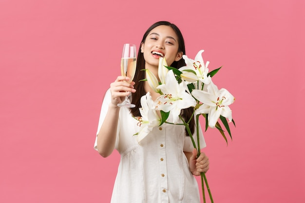 Célébration, fêtes et concept amusant. jolie femme asiatique glamour souriante en robe avec bouquet de lys blancs, levant une coupe de champagne pour faire du pain grillé, boire pour une fille d'anniversaire