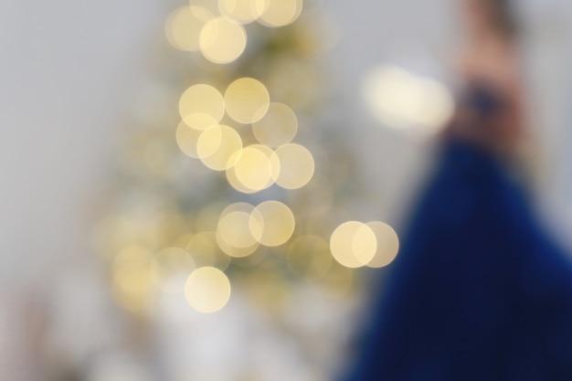 Célébration de la lumière floue sur l'arbre de noël avec fond de mur blanc femme en robe élégante
