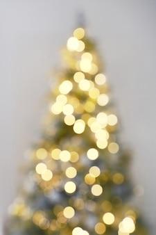 Célébration de la lumière floue sur l'arbre de noël avec fond de mur blanc. fond de vacances de défocalisation.