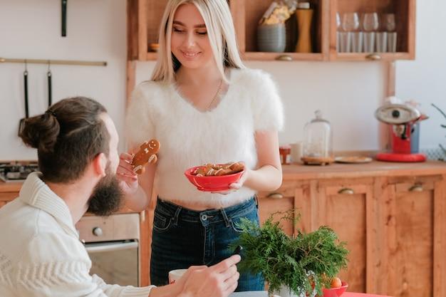 Célébration de noël. dame a préparé des biscuits de bonhomme en pain d'épice, demandant à son petit ami d'essayer.
