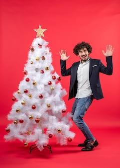 Célébration de noël avec heureux jeune homme drôle dansant et debout près de l'arbre de noël