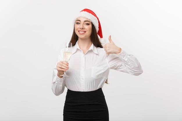 Célébration de noël jeune belle femme d'affaires célébrant noël avec verre de champagne et montrant le pouce vers le haut