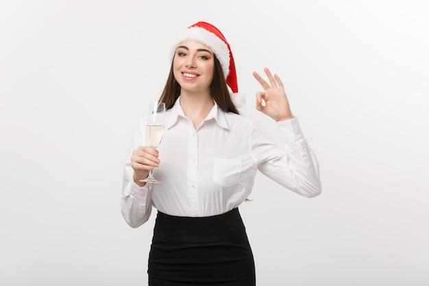 Célébration de noël jeune belle femme d'affaires célébrant noël avec verre de champagne et montrant le signe ok