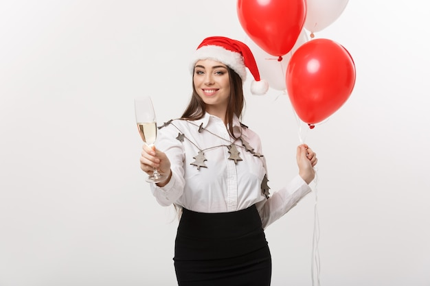 Célébration de noël - jeune belle femme d'affaires célébrant noël avec un verre de champagne et un mur de confettis.