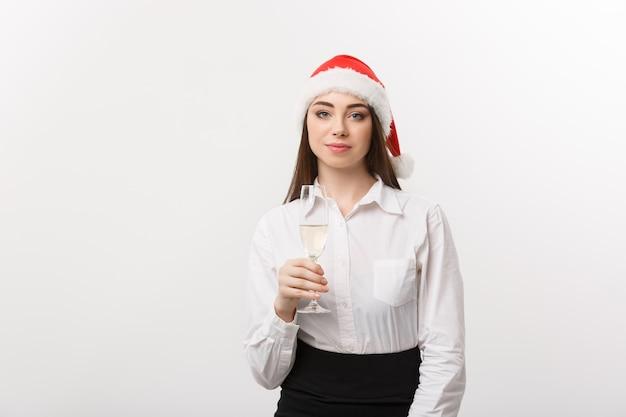 Célébration de noël jeune belle femme d'affaires célébrant noël avec un verre de champagne