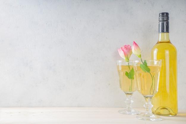 Célébration romantique de la saint-valentin. deux verres à vin blanc avec des coeurs rouges et des roses. sur l'espace de copie de fond blanc
