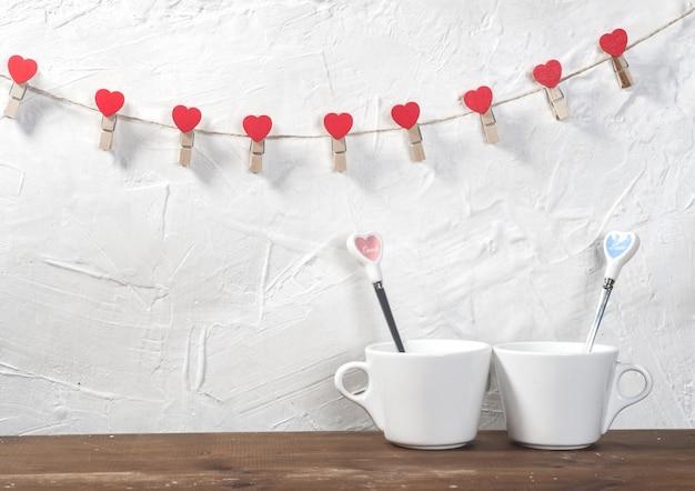 Célébration de saint valentin avec des coeurs et des tasses sur fond de bokeh