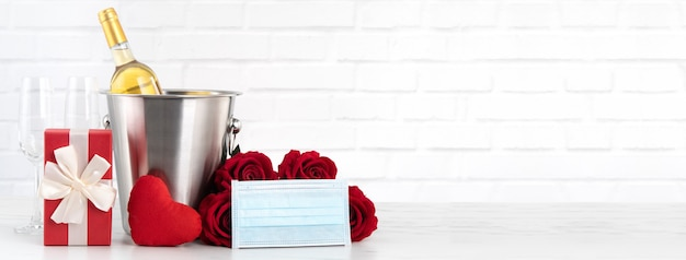 Célébration de la saint-valentin avec concept de protection de vin, de bouquet et de masque facial pendant cette période difficile.
