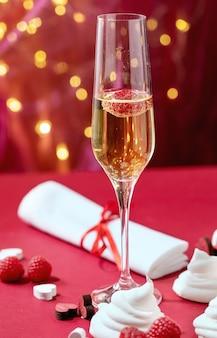 Célébration de la saint-valentin avec deux verres de champagne sur fond de bokeh léger et texture rouge