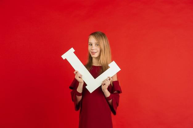 Célébration de la saint-valentin, heureuse, jolie fille caucasienne tenant une lettre sur fond de studio rouge.
