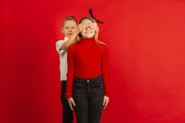 Célébration de la saint-valentin, heureux, mignons enfants caucasiens isolés sur studio rouge