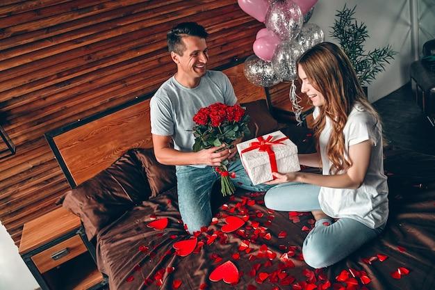 Célébration de la saint-valentin. un homme offre un cadeau et des roses rouges à une femme. un couple est assis sur le lit avec des confettis en forme de cœur.