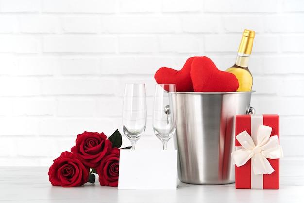 Célébration de la saint-valentin avec vin, cadeau et bouquet de roses pour les voeux de vacances.