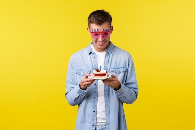 Célébration vacances et personnes émotions concept rêveur heureux et touché petit ami tenant un gâteau d'anniversaire fait maison se sentir joyeux comme faire souhait sur mur jaune bougie allumée