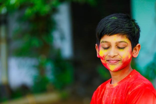 Célébrations de holi - petit garçon indien jouant à holi et montrant l'expression du visage.