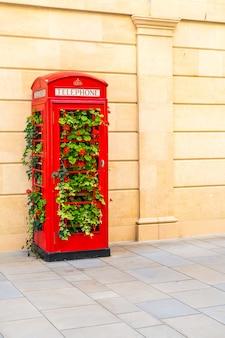 Célèbre cabine téléphonique rouge à londres avec des feuilles