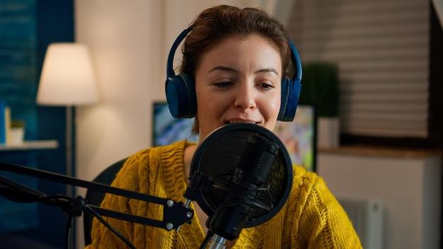 Célèbre femme organisant un microphone professionnel et souriant tout en enregistrant un podcast pour les médias sociaux depuis la maison la nuit. production en ligne en ligne, diffusion sur internet, animateur d'émissions diffusant du contenu en direct