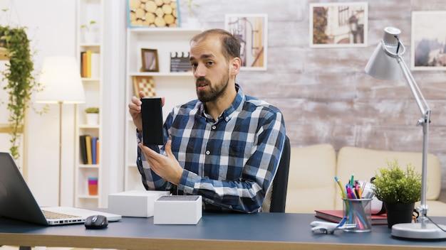 Célèbre influenceur enregistrant le déballage d'un téléphone moderne. créateur de contenu créatif.