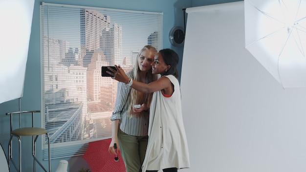 Célèbre modèle noir faisant selfie avec maquilleuse