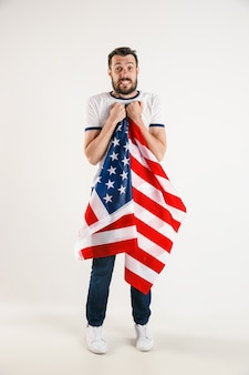 Célébrer un jour de l'indépendance. étoiles et rayures. jeune homme avec le drapeau des états-unis d'amérique isolé sur le mur blanc du studio. semble fou heureux et fier comme un patriote de son pays.