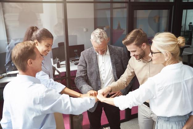 Célébrer le succès d'un groupe d'hommes d'affaires multiraciaux heureux faisant des coups de poing en se tenant debout