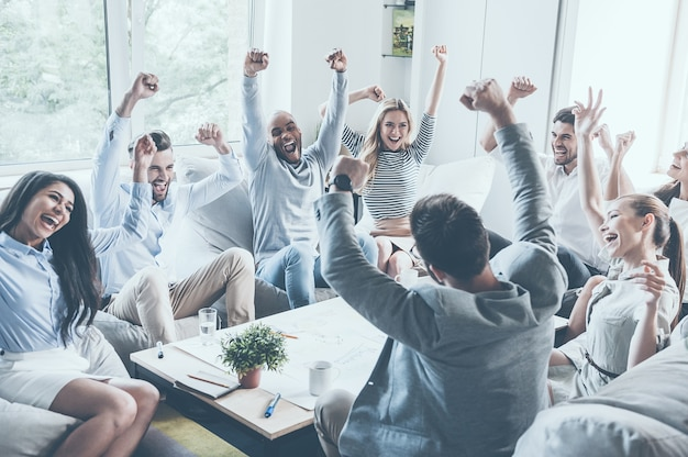 Célébrer le succès. groupe de jeunes gens d'affaires levant les bras et ayant l'air heureux assis ensemble autour du bureau