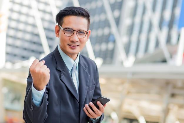 Célébrer le succès. heureux homme d'affaires en se tenant debout à l'extérieur avec l'immeuble de bureaux en arrière-plan
