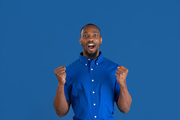 Célébrer la victoire. portrait monochrome de jeune homme afro-américain isolé sur mur bleu. beau modèle masculin. émotions humaines, expression faciale, ventes, concept publicitaire. la culture des jeunes.