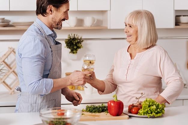 Célébrer le week-end en famille. charmant homme d'âge mûr charismatique debout dans la cuisine et souriant tout en dégustant un verre de vin avec sa mère vieillissante