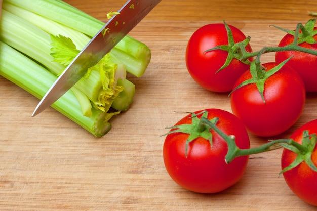 Céleri et tomates sur une planche à découper