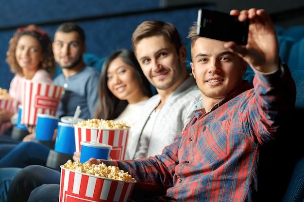 Celui-ci est pour une bonne mémoire. groupe d'amis joyeux joyeux prenant selfie ensemble assis dans une salle de cinéma locale