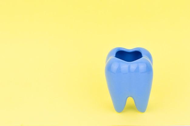 Cendrier en forme de dent en céramique bleue sur fond jaune.