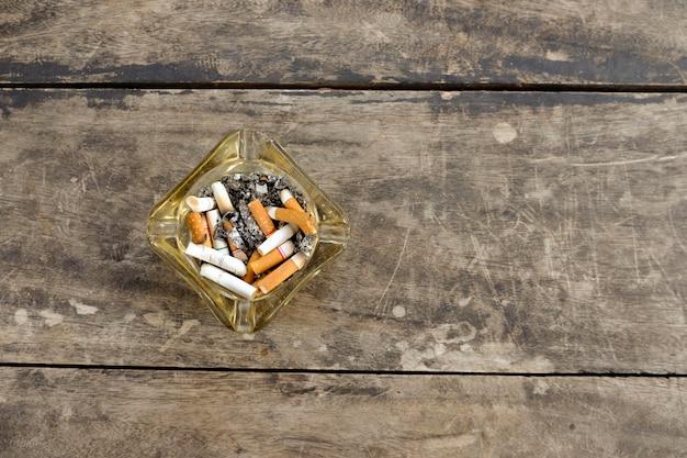 Cendrier plein de mégots de cigarettes sur fond en bois