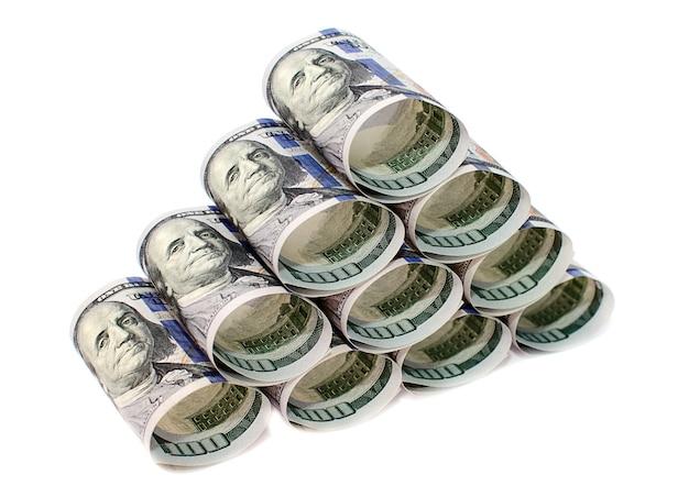 Cent billets d'un dollar roulés et empilés dans une pyramide isolée sur une surface blanche
