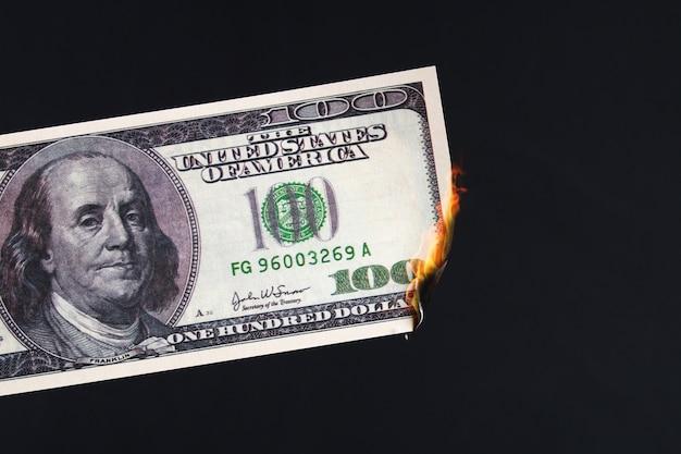 Cent dollars américains brûlant dans une flamme de feu. effondrement du dollar. dévaluation. chute de monnaie
