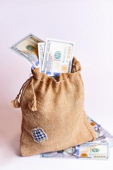 Cent dollars dans un sac de toile de jute sur fond blanc.