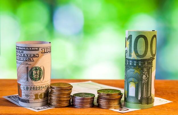 Cent euros et cent dollars américains des billets de banque roulés, avec des pièces en euros et des cents américains sur fond flou vert flou.