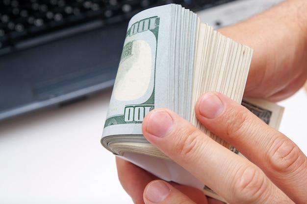 Des centaines de dollars dans une pile tiennent une main masculine sur un ordinateur portable