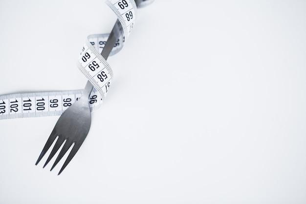 Centimeter avec du ruban adhésif et une fourchette sur un blanc avec une place pour insérer du texte